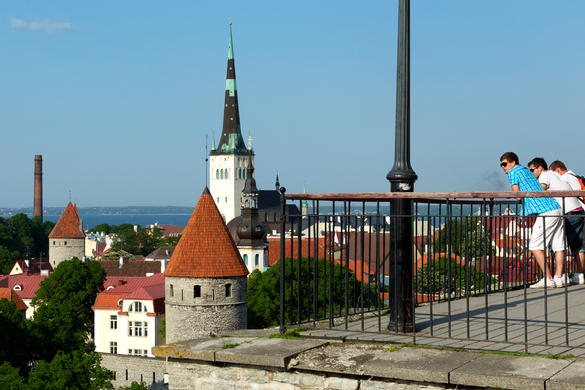 People enjoying the view of the Old Town and Oleviste church tower at the Patkuli viewing platform in Tallinn, Estonia.