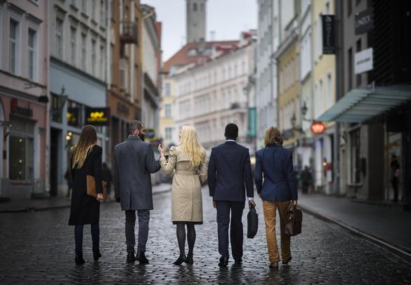 A group of business people walking on the streets of Tallinn Old Town in autumn