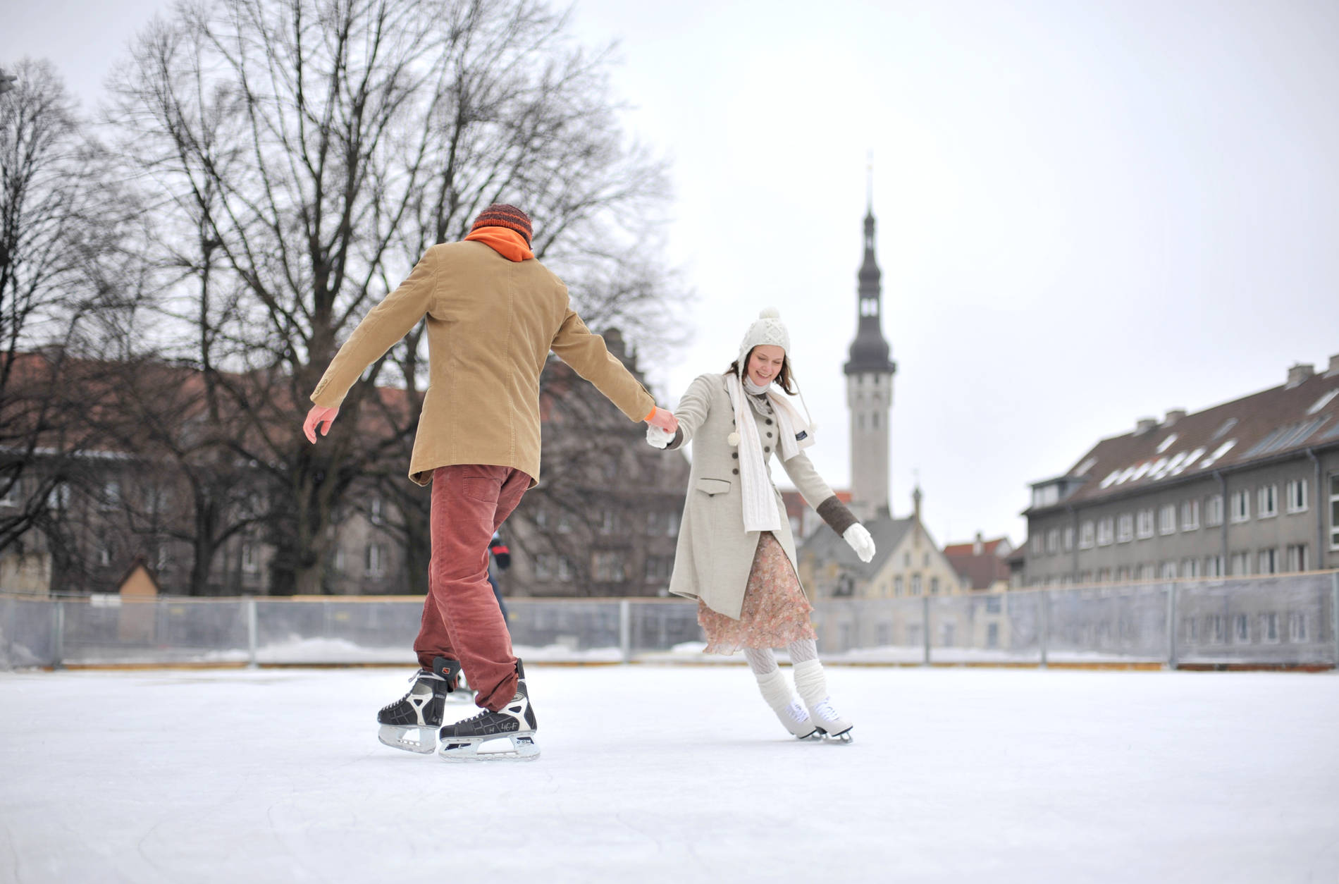 Couple ice skating at the ice rink in the Old Town of Tallinn, Estonia