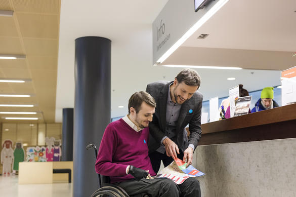 Two men, one in a wheelchair, are looking at a brochure in KUMU art museum in Tallinn