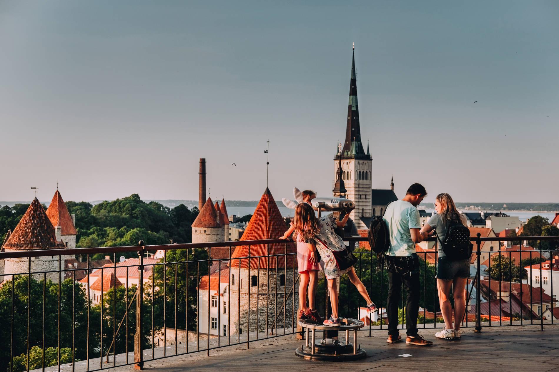inimesed Patkuli vaateplatvormil Tallinnas Toompeal suveõhtul, taustal linnamüüri tornid ja Oleviste kirik
