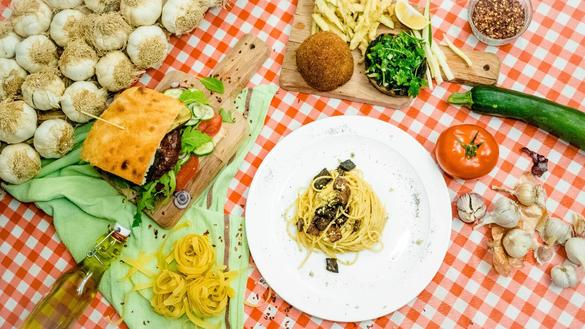 Vegetarian pasta dish and a hamburger which were made in the Vegan Italy restaurant. The restaurant is located in Tallinn, Estonia.