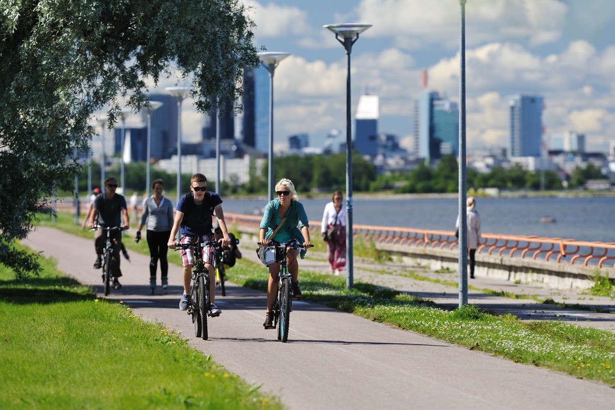 Велосипедисты на Пиритаском променаде летом на фоне силуэта современного Таллинна, Пирита, Таллинн, Эстония
