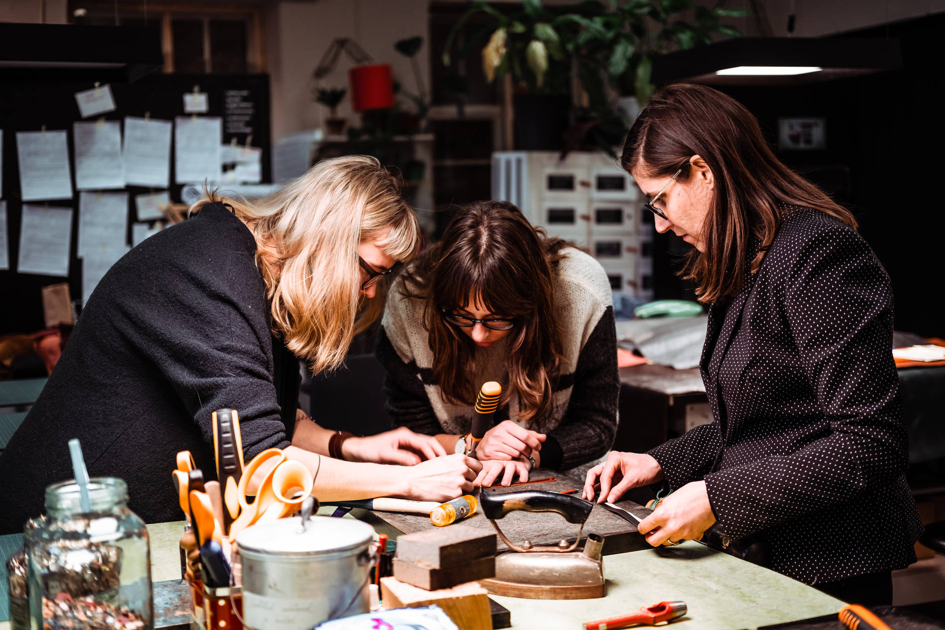 People crafting with leather at the Stella Soomlais leather workshop.