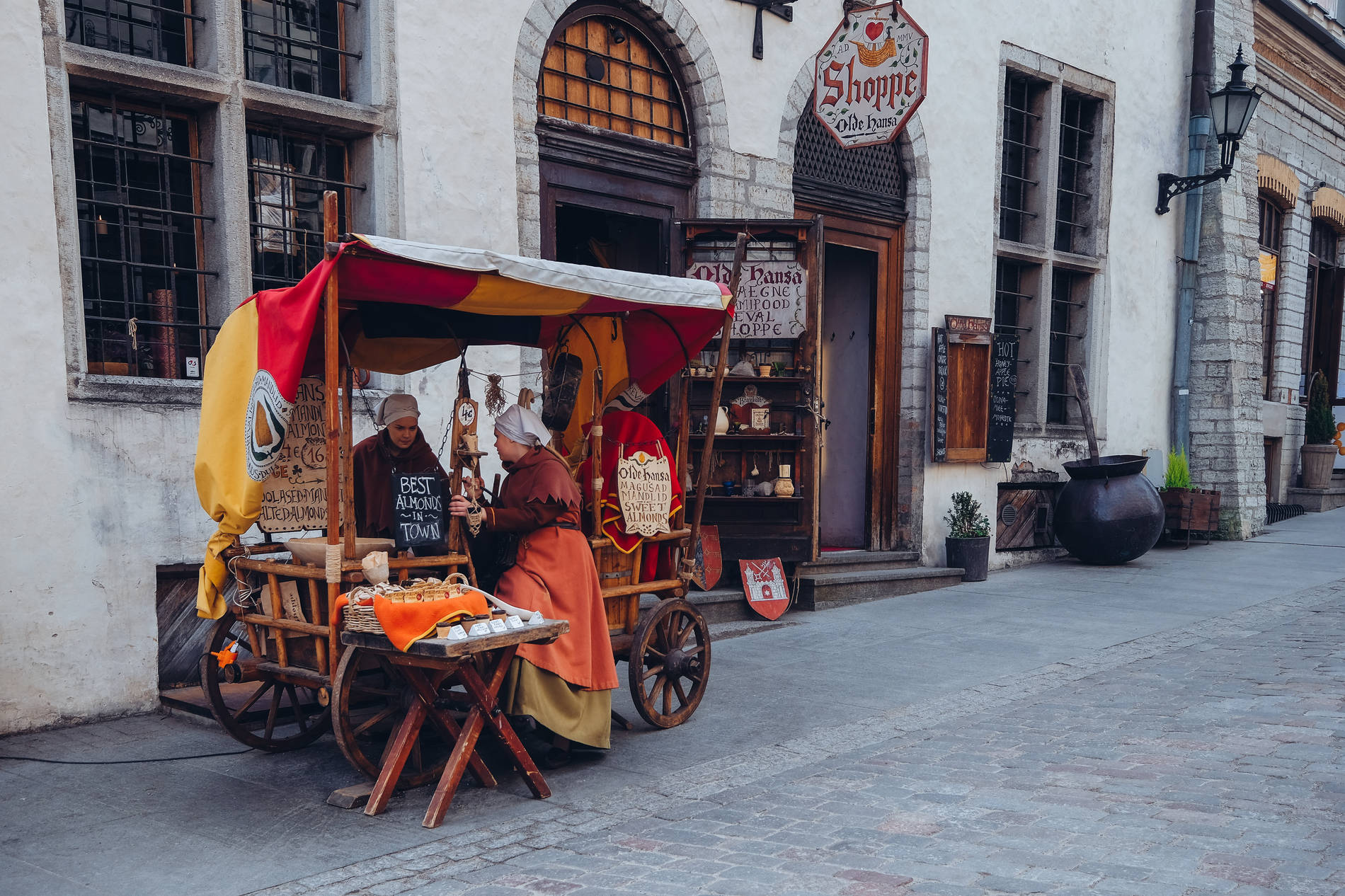 Almond cart of the Olde Hansa restaurant with two women in medieval costumes in the Old Town of Tallinn, Estonia.