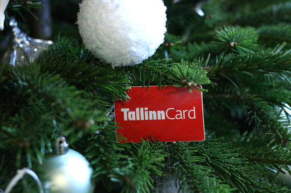 The red plastic Tallinn Card with white Christmas baubles and green spruce branches.