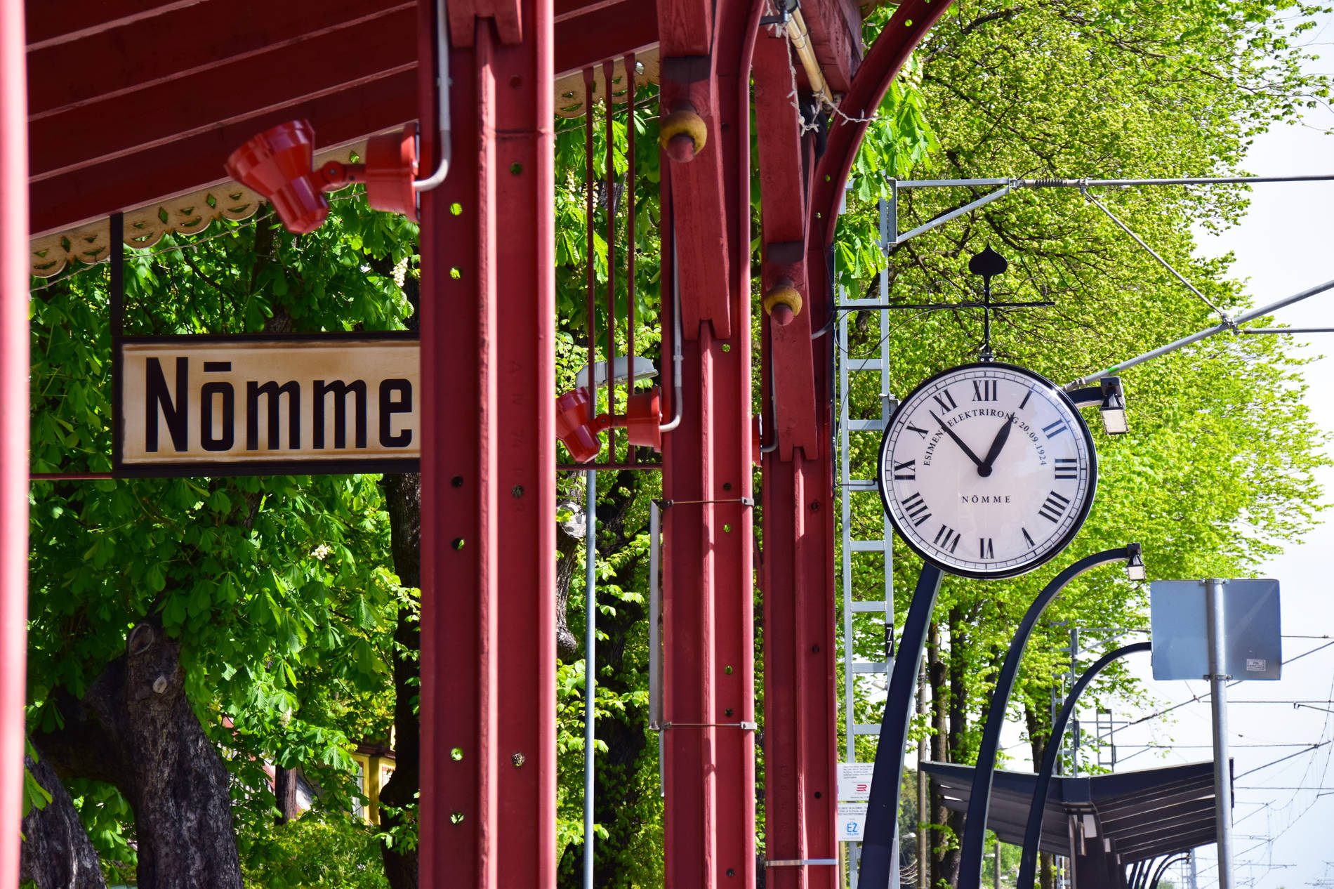 Detail of Nõmme rain station, showing a clock and the sign of Nõmme.