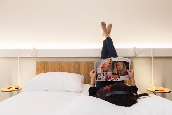 Женщина, лежа на кровати, читает журнал в номере гостиницы ibis, Центр города, Таллинн, Эстония