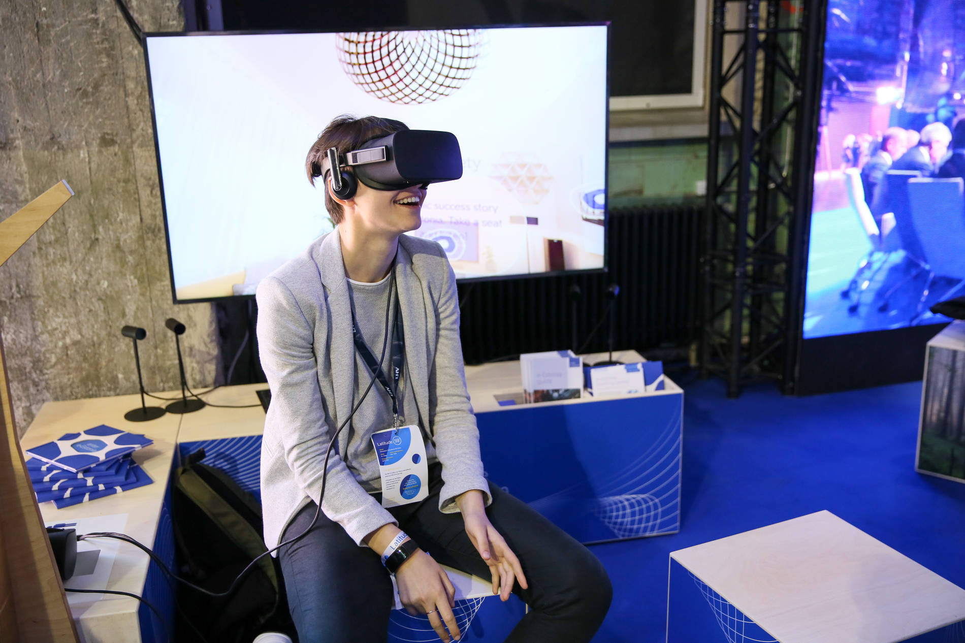 A woman smiling when wearing virtual reality glasses and experiencing virtual reality.