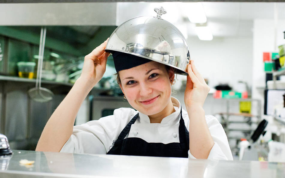 A cook with a bowl on her head smiling